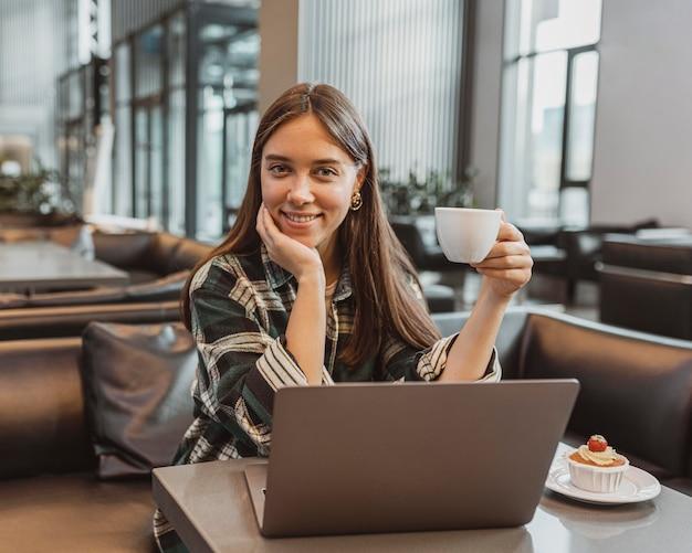 Bela jovem fazendo uma pausa para o café