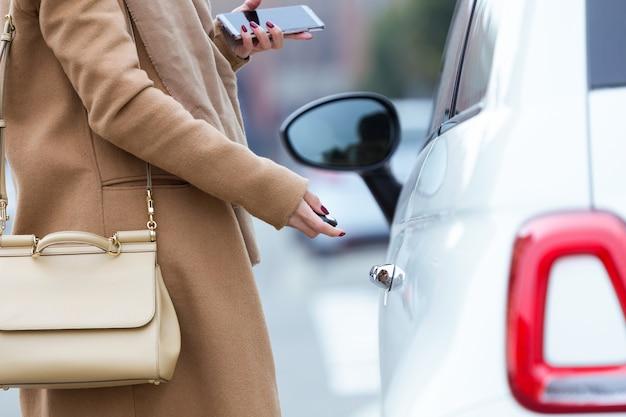 Bela jovem fechando seu carro.