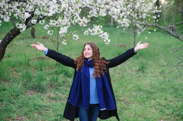 Bela jovem feliz andando em um jardim de primavera desabrochando