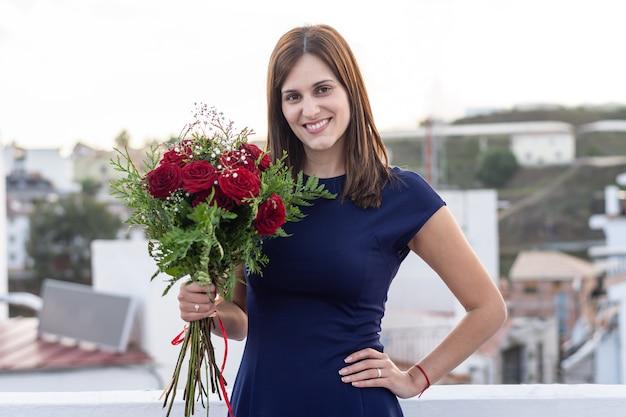 Bela jovem feliz com buquê de rosas vermelhas
