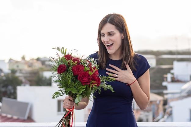 Bela jovem feliz e surpreendida com seu buquê de rosas vermelhas