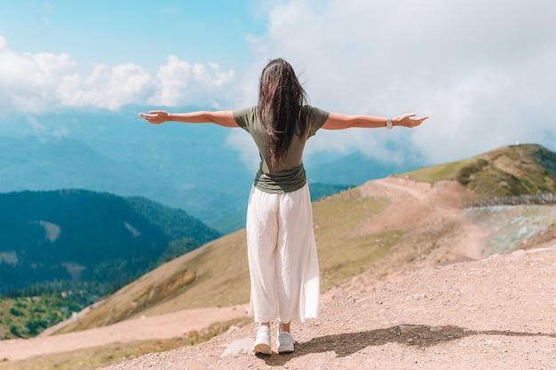 Bela jovem feliz nas montanhas ao fundo de nevoeiro
