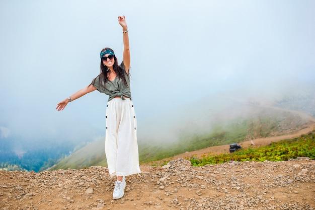 Bela jovem feliz nas montanhas