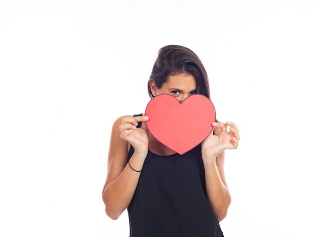Bela jovem feliz que está segurando um grande coração vermelho para o dia dos namorados