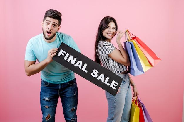 Bela jovem feliz sorridente casal homem e mulher com sinal de venda final e sacolas coloridas