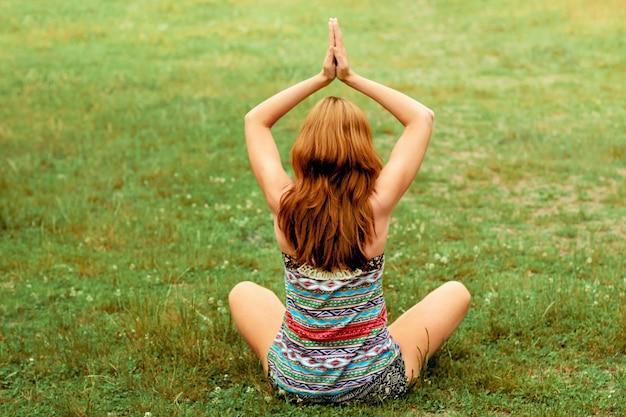 Bela jovem fêmea relaxa em pose de ioga na natureza verde. mulher de beleza fazendo ioga. conceito de saudável e ioga. fitness e esportes