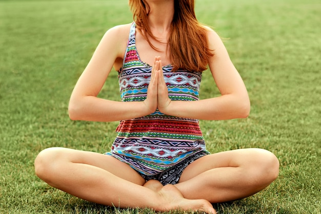 Bela jovem fêmea relaxa em pose de ioga na natureza verde.