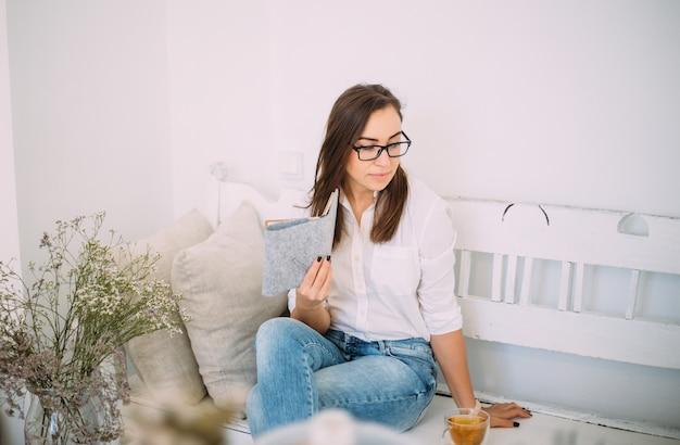 Bela jovem feminina em copos elegantes, vestidos com roupas casuais da moda se senta em um banco com um notebook e uma xícara de chá