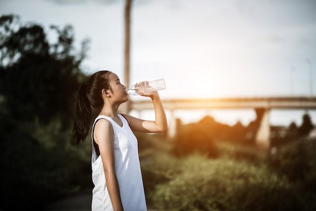 Bela jovem fitness mulher bebendo água depois de executar o exercício
