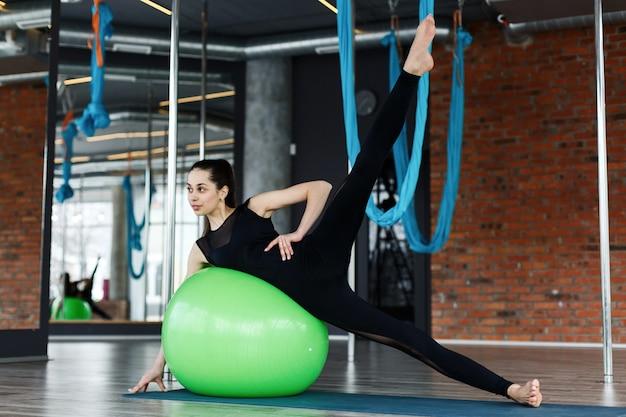 Bela jovem flexionando muscels abdominais na bola verde no ginásio