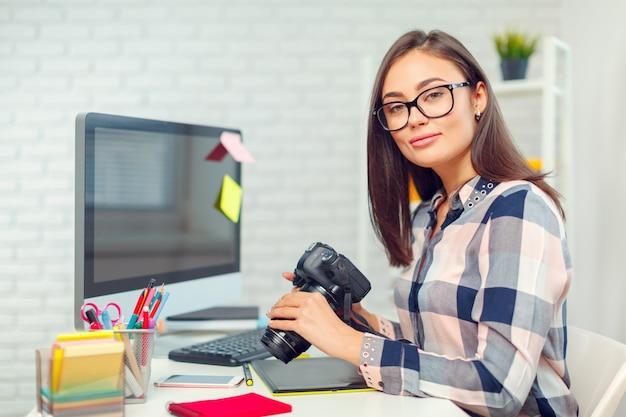 Bela jovem fotógrafo com câmera no escritório