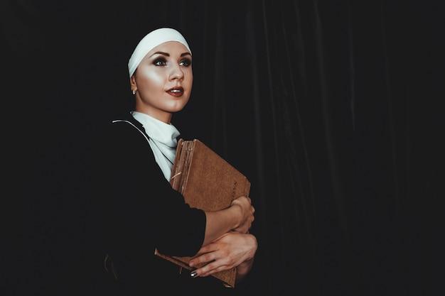 Bela jovem freira em um terno preto religião contém bíblia e posando para a câmera com um grande livro sobre um fundo preto. conceito de religião.