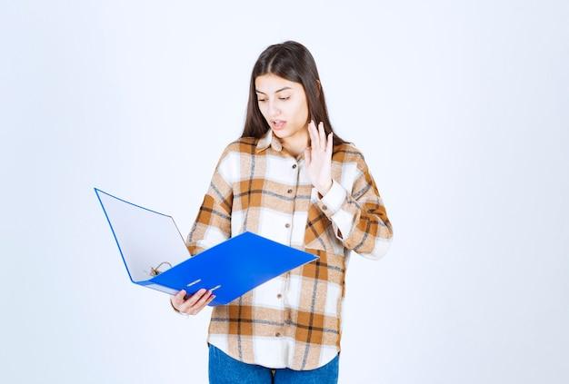 Bela jovem funcionária olhando documentos dentro da pasta azul.