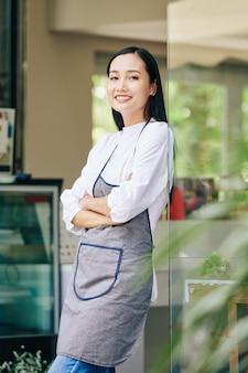 Bela jovem garçonete asiática parada na porta de sua cafeteria e sorrindo na frente