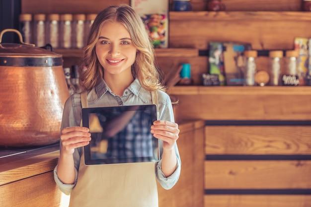 Bela jovem garçonete no avental está mostrando um tablet.