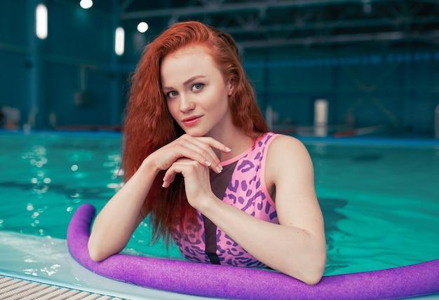 Bela jovem garota ruiva na piscina interior