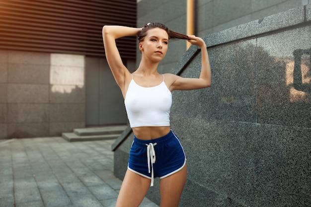 Bela jovem garota sexy atleta descansando depois de um treino atlético duro em uma rua da cidade