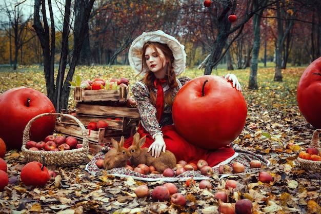 Bela jovem garota sexy com maçãs vermelhas no jardim de outono