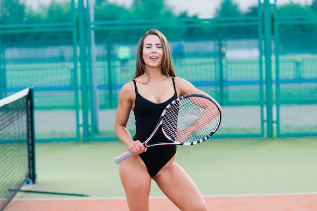 Bela jovem garota sexy de esportes gratuitos fitness vestida com macacão em uma quadra de tênis