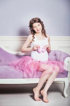 Bela jovem grávida com botinhas de malha rosa e uma saia de balé rosa em fundo retrô