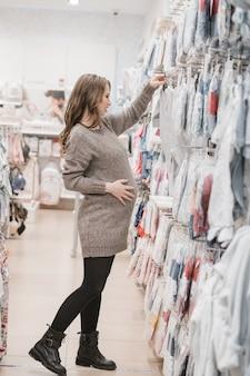 Bela jovem grávida escolhendo o carrinho de bebê ou carrinho de bebê para o recém-nascido.