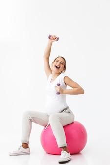 Bela jovem grávida fazendo exercícios de esporte com uma bola de fitness isolada sobre um fundo branco, segurando halteres