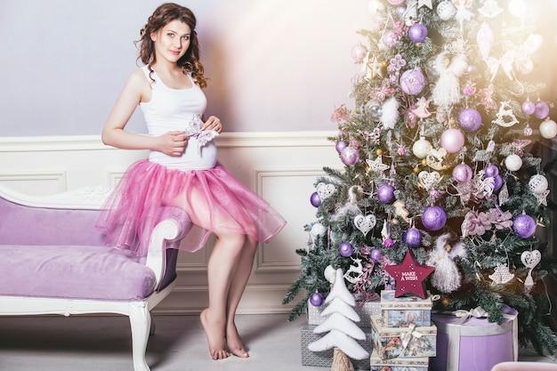 Bela jovem grávida no natal com uma linda árvore de natal decorada com