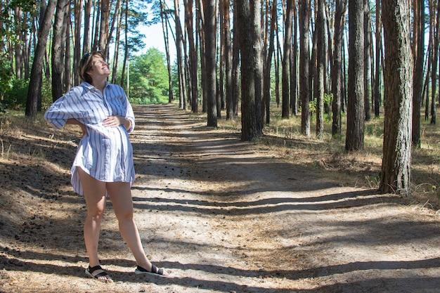 Bela jovem grávida respirando profundamente ao ar livre no parque