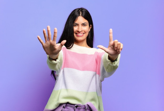 Bela jovem hispânica sorrindo e parecendo amigável, mostrando o número sete ou sétimo com a mão para a frente, em contagem regressiva