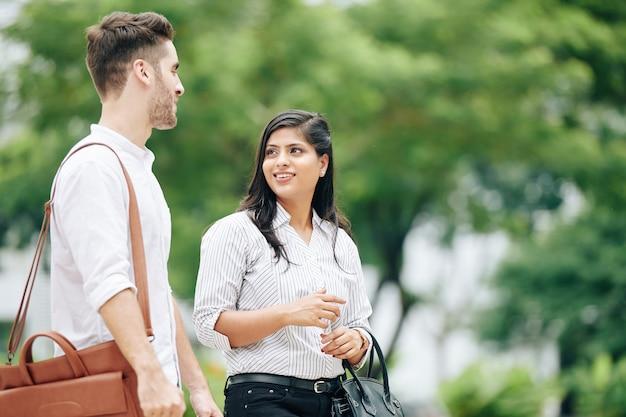 Bela jovem indiana conversando com um colega ao caminhar ao ar livre depois do trabalho