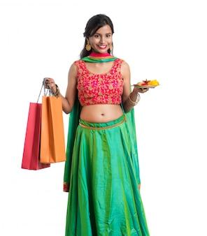 Bela jovem indiana segurando e posando com sacolas de compras e pooja thali em uma parede branca