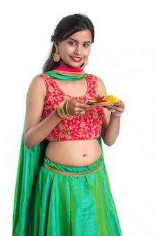 Bela jovem indiana segurando pooja thali ou realizando adoração em branco