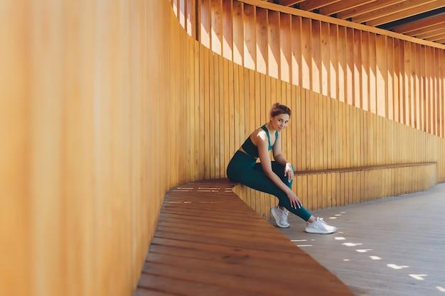 Bela jovem instrutor de fitness dá aulas em vídeo usando o laptop em uma varanda de madeira na rua.