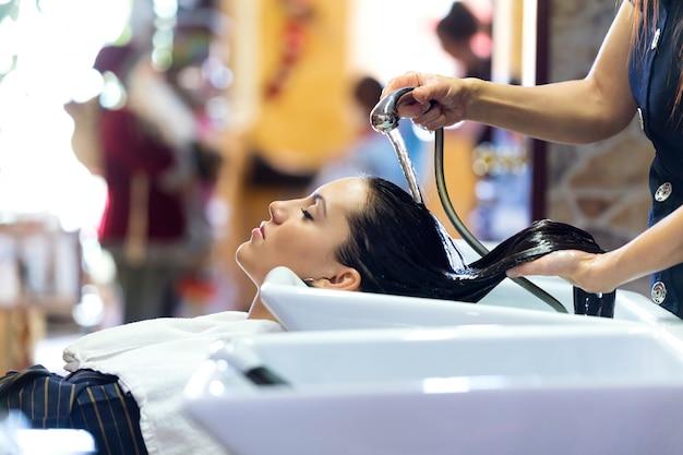Bela jovem lava os cabelos em um salão de beleza.