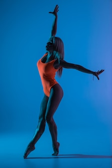 Bela jovem legal cabe mulher ginasta no vestido azul sportswear malhando, realizando o elemento de ginástica art, pulando, fazendo o salto no ar, dançando