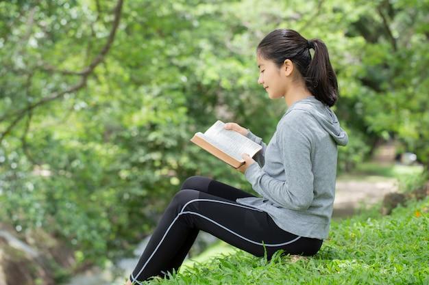 Bela jovem lendo a bíblia no parque. lendo um livro. conceito da bíblia de deus é baseado na fé e espiritualidade.