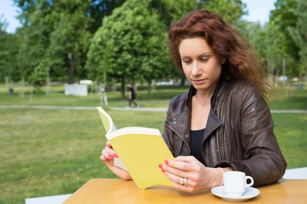 Bela jovem lendo livro no café da faculdade