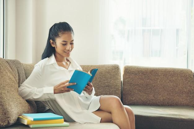 Bela jovem lendo livro perto da janela em casa