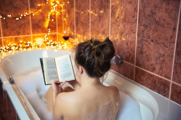 Bela jovem lendo um livro e bebendo vinho tinto na banheira com espuma de espuma, decorada com luzes coloridas, conceito relaxante e spa