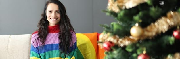 Bela jovem lésbica sorrindo e sentada no sofá perto da árvore de natal