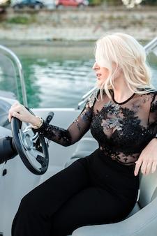 Bela jovem loira, andar de barco na água.