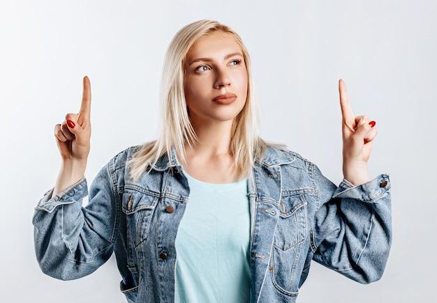 Bela jovem loira aponta seus dedos para o topo em um fundo cinza isolado
