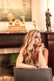 Bela jovem loira caucasiana em um vestido de baile preparado na bela sala de estar do hotel ao lado de uma lareira