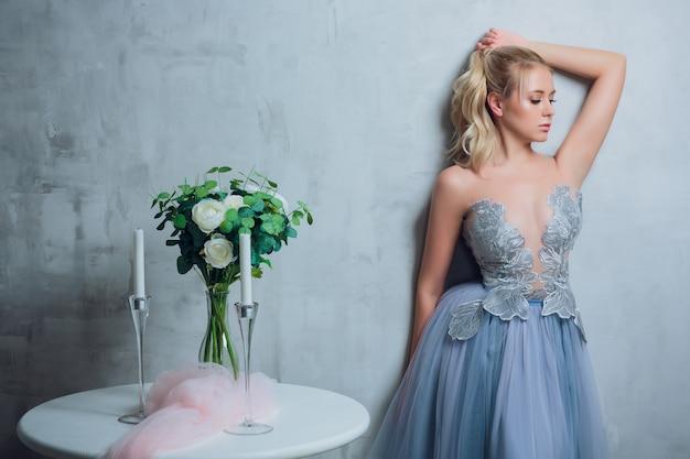 Bela jovem loira com cabelo desarrumado no coque em vestido bege pastel na parede cinza