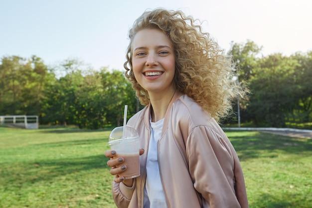 Bela jovem loira com cabelo encaracolado caminhando no parque, bebendo um smoothie
