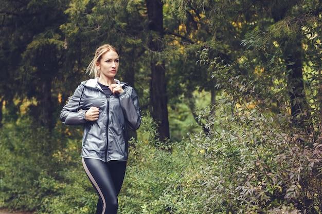 Bela jovem loira com cabelos longos está correndo no parque no dia chuvoso,