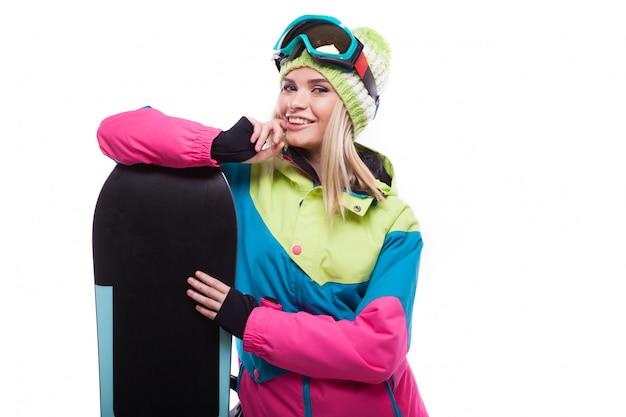 Bela jovem loira com casaco de neve colorido segurar snowboard
