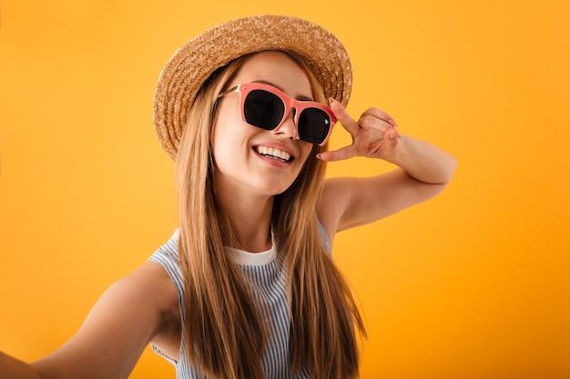 Bela jovem loira com chapéu de verão e óculos escuros Foto Premium