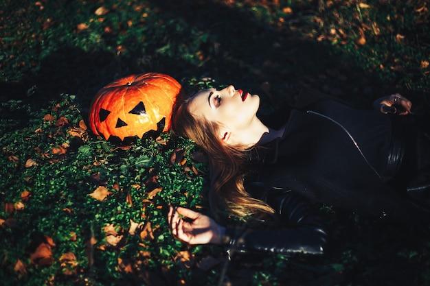 Bela jovem loira com maquiagem extravagante em uma jaqueta de couro preta