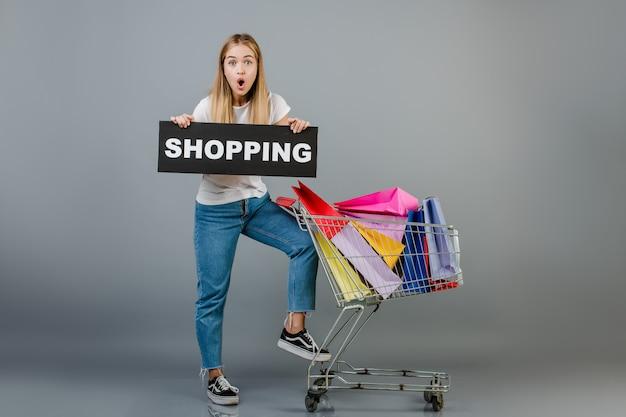 Bela jovem loira com sinal de compras e carrinho de mão com sacolas coloridas isoladas sobre cinza